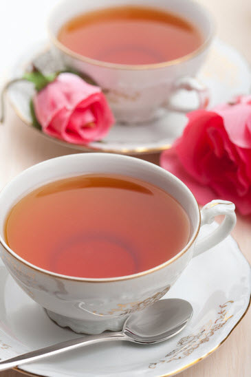 Two fancy cups of tea, with roses